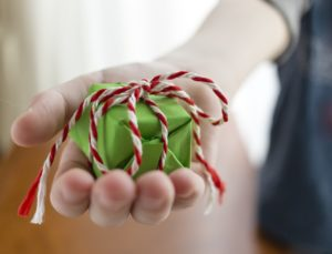 hand giving a christmas gift. one more present I hope you will give to everyone on your list.