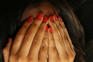 Woman covering her face in shame