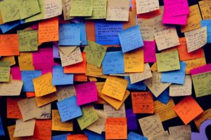 Bulletin board crowded with too many notes.