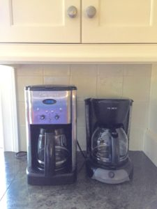 Two coffee pots sitting on a kitchen counter next to each other.