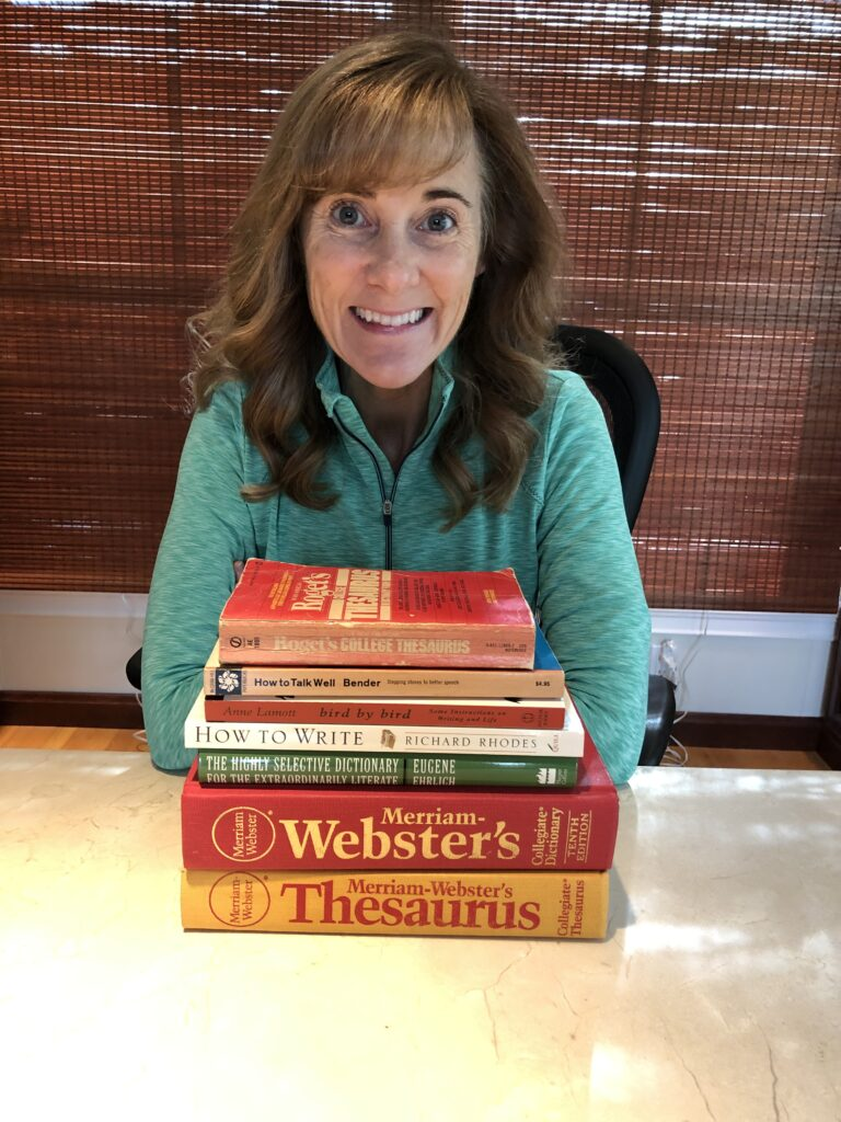 Seana with a stack of books giving ideas on how to declutter.