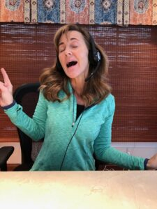 Seana singing with headphones on while listening to a playlist.