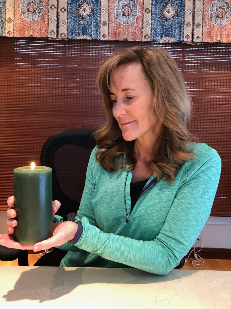 Seana with a candle talking about enhancing the air around you.