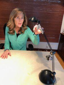 Seana turning on a task light at her desk.
