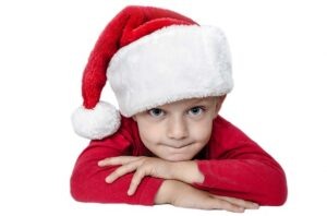 Boy in a santa hat. What to do when it feels like children get more than they can even enjoy.